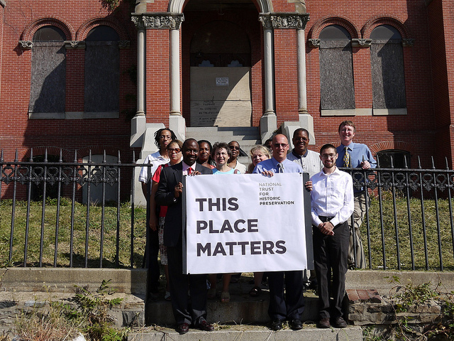 "A group of people standing in front of the Hebrew Orphan Asylum holding a sign reading ""This Place Matters"""