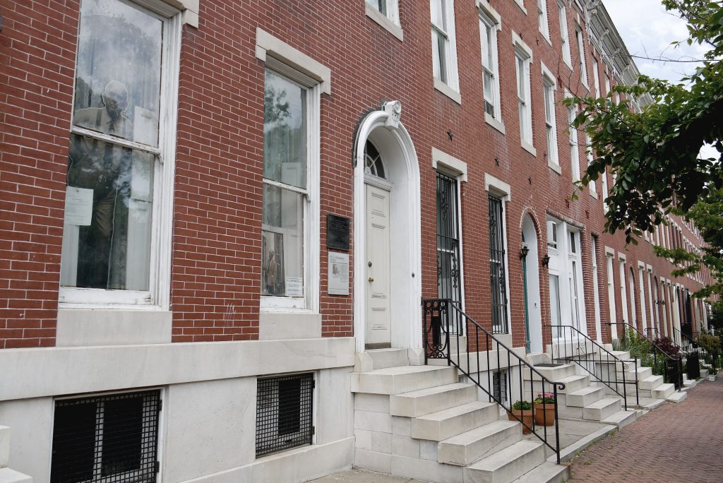 A red brick rowhouse with white marble steps and trim.
