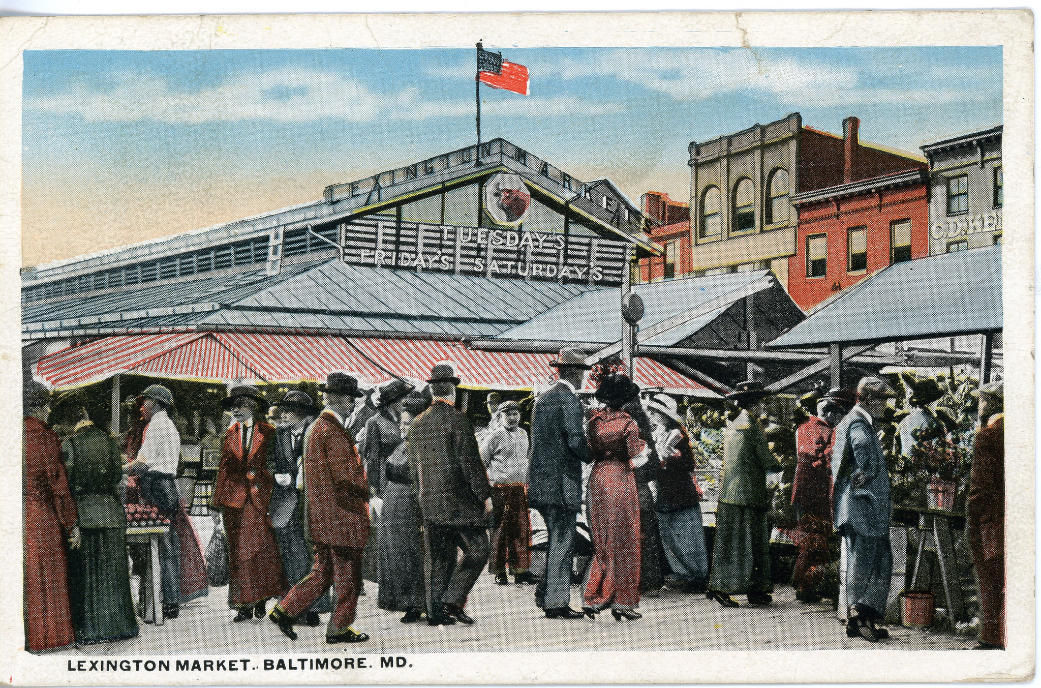 Colorized postcard of people standing around market stalls in front of the Lexington Market shed building.