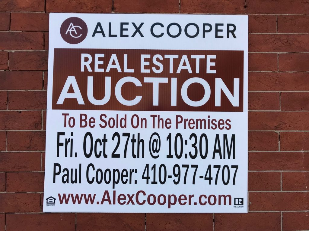 "A sign reading: ""Alex Cooper Real Estate Auction To Be Sold On the Premises Fr/ Oct 27th @ 10:30 AM Paul Cooper 410-977-4707 www.AlexCooper.com"""