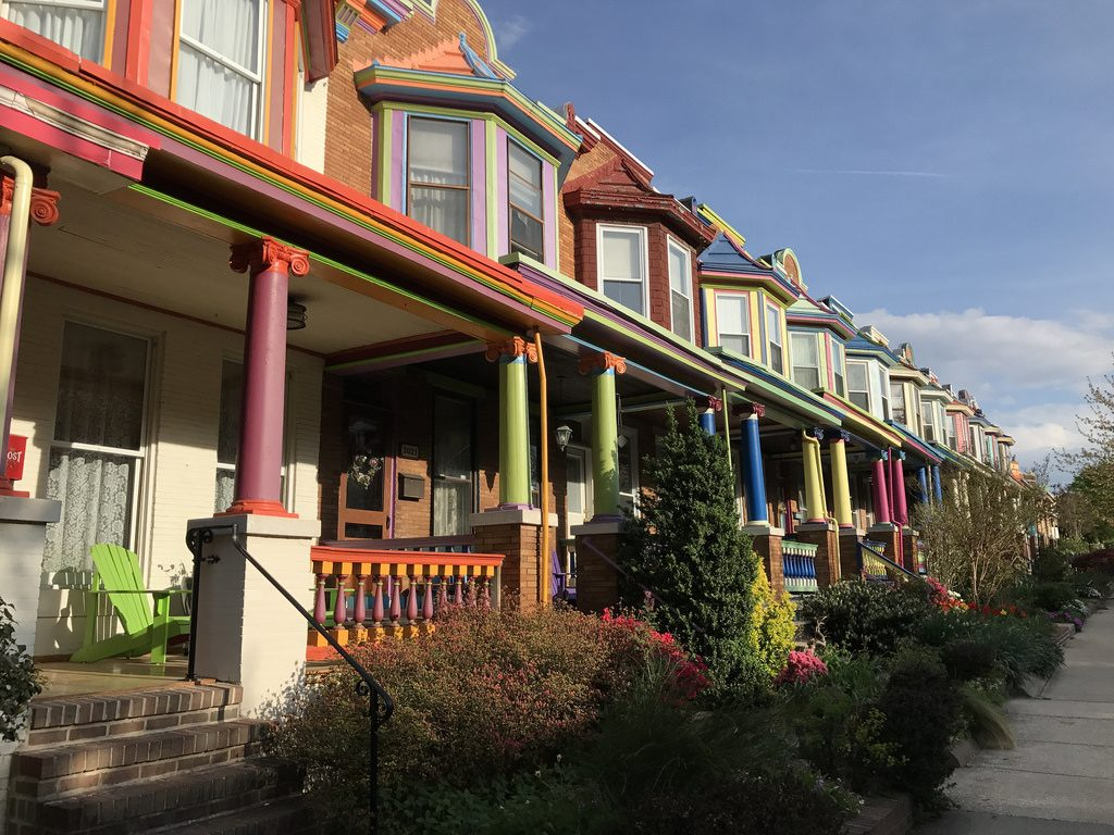Rowhouses with colorfully painted porches and bay windows.