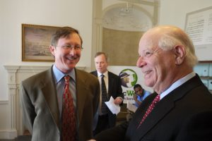 Two men, Johns Hopkins and Sen. Ben Cardin, both wearing dark suits and red ties in a room at Clifton Mansion.