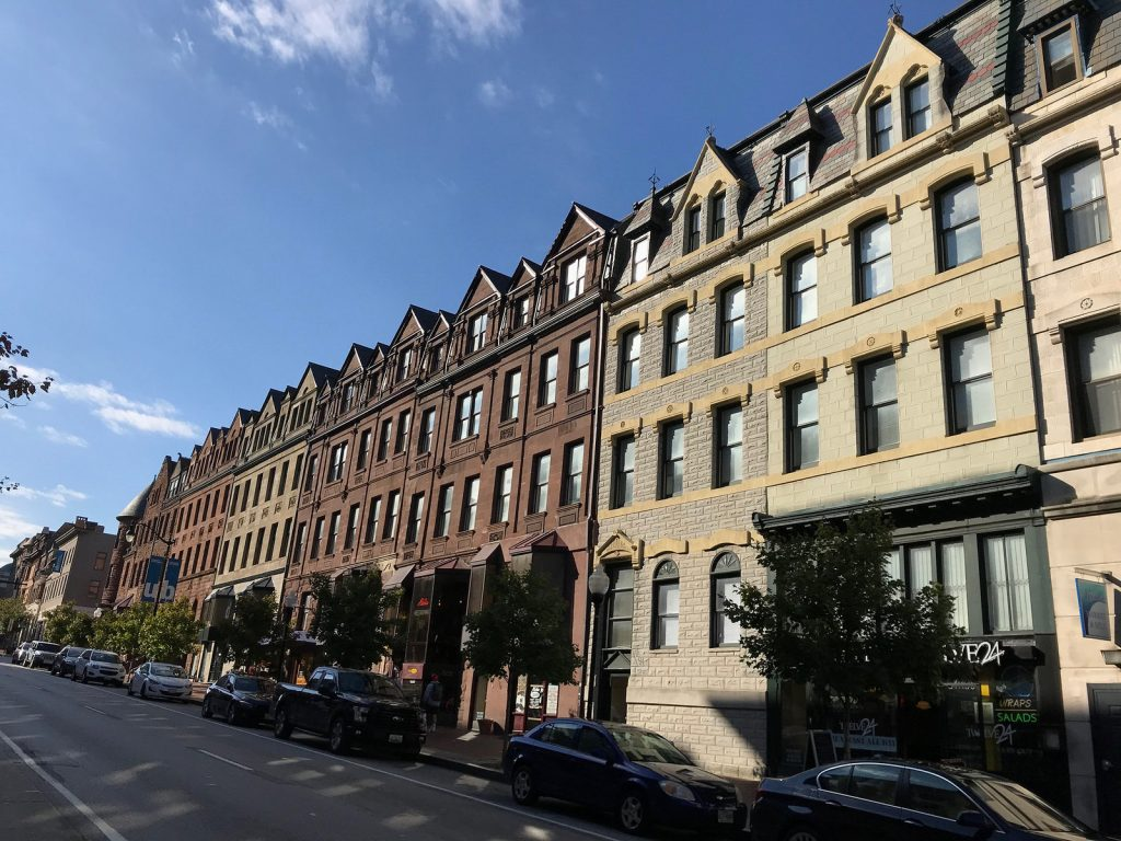 A block of stone-faced four-story rowhouses with a clear blue sky in the background.