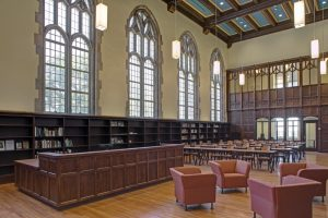 A large room with tall arched windows, padded chairs, and long bookshelves.