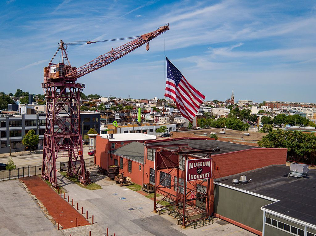 Brick museum building and a large steel crane holding a U.S. flag above the building.