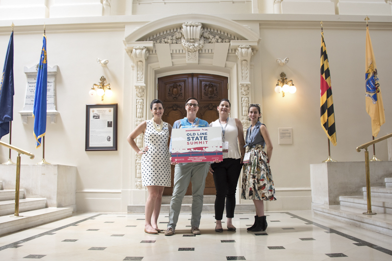 Four women standing in front of an ornate interior door holding a sign that read Old Line State Summit.
