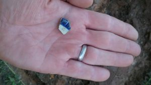 blue and white ceramic fragment the size of a dime