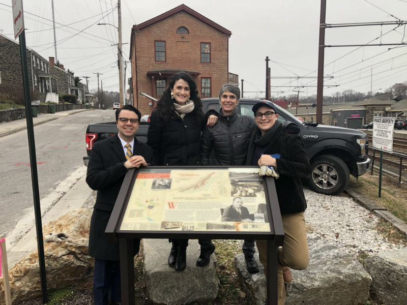 A group of Preservation Maryland staff standing behind an interpretive sign at Clipper Mill.