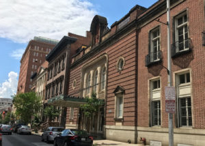 A streetscape showing a brick former theater building next to a large brownstone house.