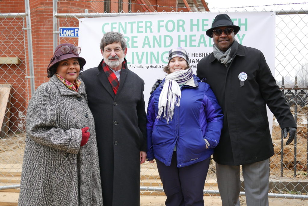 A group of four people standing in front of a sign reading Center for Health Care and Healthy Living