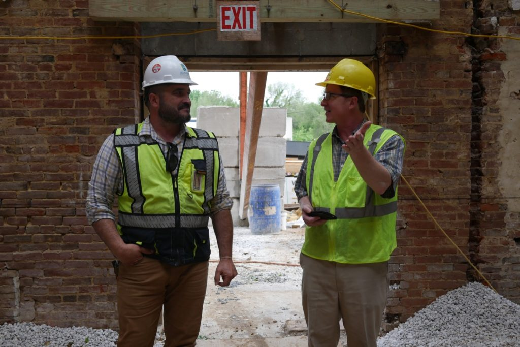 Two men wearing neon yellow vests and hard hats in with a brick wall and construction site in the background.