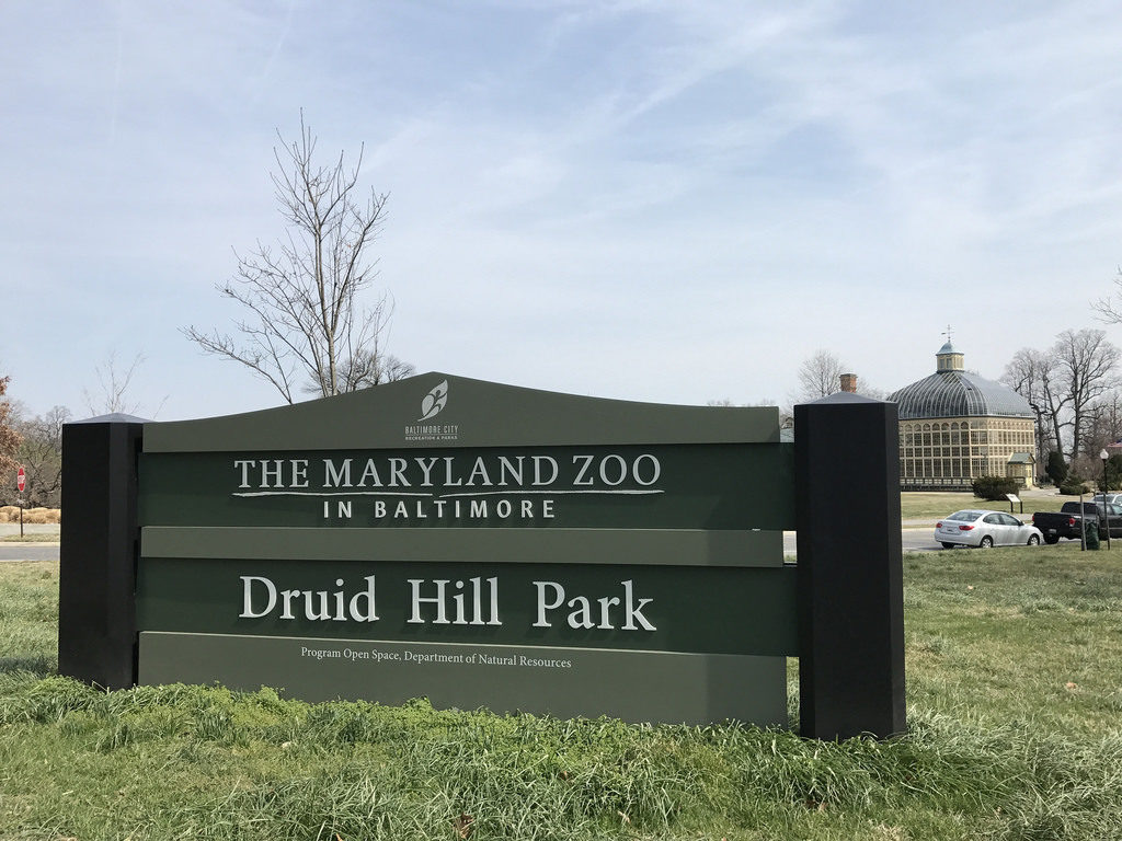 Entrance sign at Druid Hill Park with the Conservatory in the background.