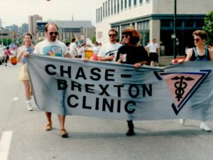 "A group of three people walking holding a large sign that reads ""Chase-Brexton Clinic"""
