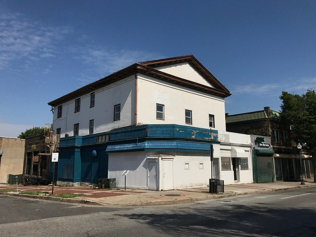 A large corner building painted white with blue trim around a first floor storefront.