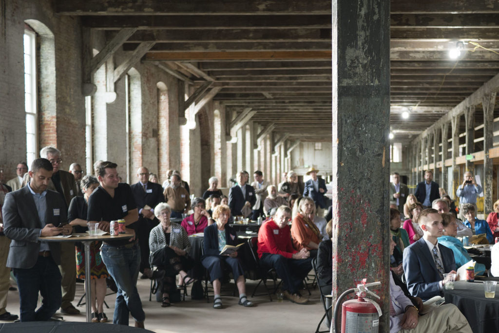 Crowd of people sitting and standing within a large industrial space.