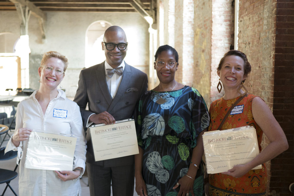 A group of four people holding award certificates