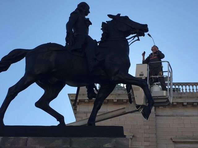 Monument conservation in action: a man in a cherry picker lift cleans the mouth of the horse that Marquis de Lafayette rides